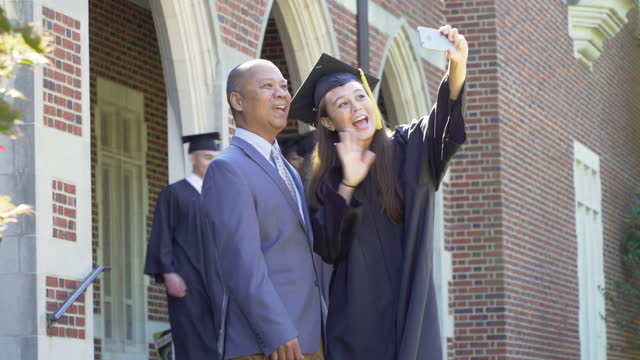 father and daughter at graduation taking a selfie - cap stock videos & royalty-free footage