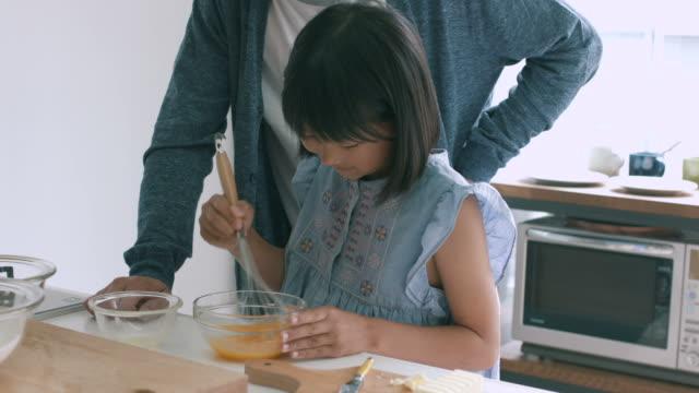 父と娘焼く一緒 - 娘点の映像素材/bロール