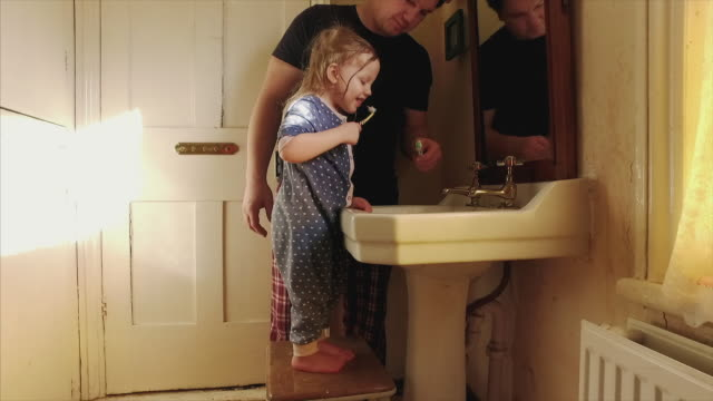 Father and daughter brushing their teeth together