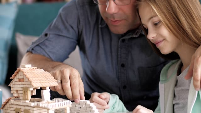 Father and daughter building house model together