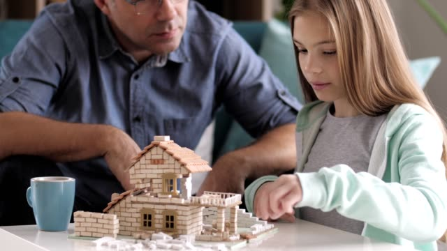 father and daughter building model house together - coffee table stock videos & royalty-free footage