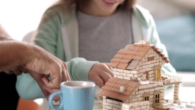Father and daughter building model house together