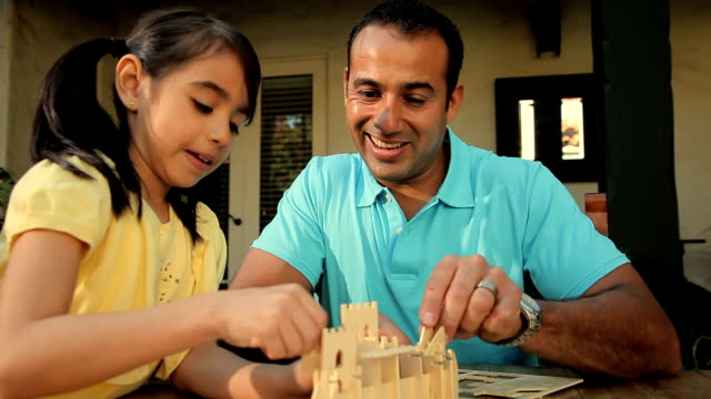 ms father and daughter building wooden model together / los angeles, california, usa - haarzopf stock-videos und b-roll-filmmaterial