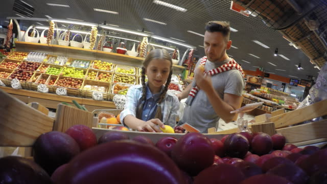 POV Father and daughter choosing fruits in supermarket