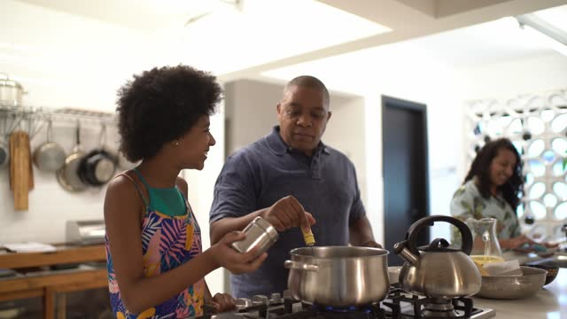 father and daughter cooking together at home - genderblend stock videos & royalty-free footage