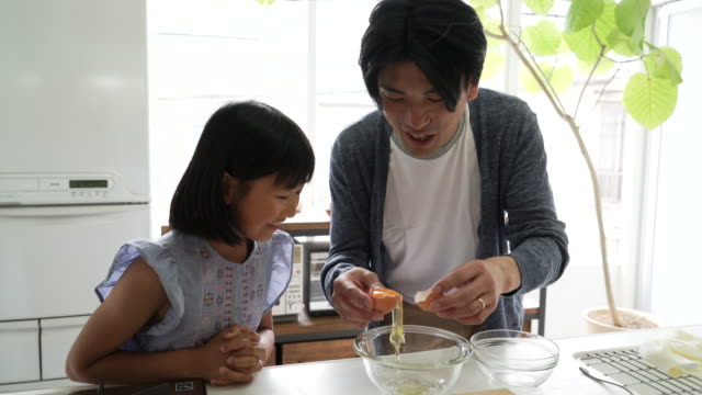 Father and daughter cooking together in the kitchen