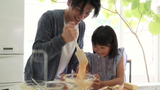 台所で一緒に調理する父と娘 - オーブンの天板点の映像素材/bロール