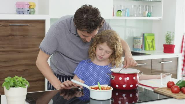 vídeos de stock, filmes e b-roll de father and daughter cooking - espaguete