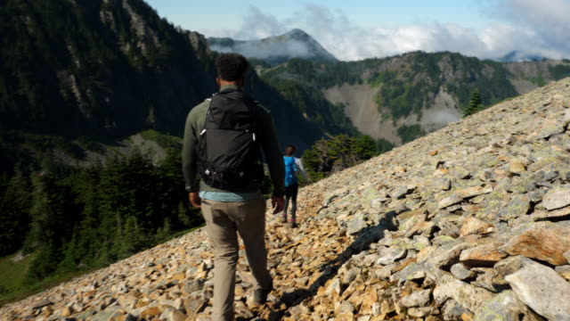 vidéos et rushes de swish father and daughter crossing rock field during hike in mountains - montrer la voie