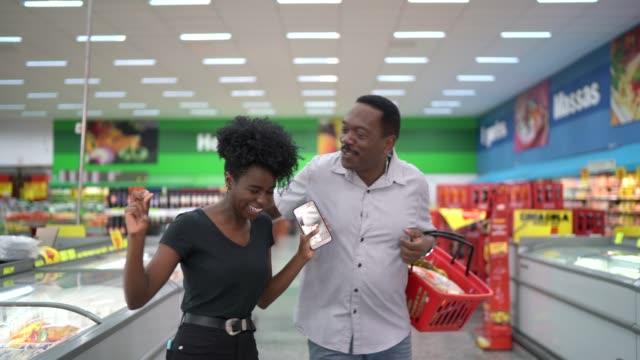 vidéos et rushes de danse de père et de descendant et ayant l'amusement dans le supermarché - panier courses