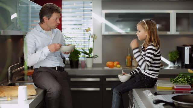 MS Father and daughter (10-11) eating cornflakes in kitchen / Kleinmachnow, Brandenburg, Germany