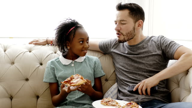 father and daughter eating pizza and watching tv - adoption stock videos and b-roll footage