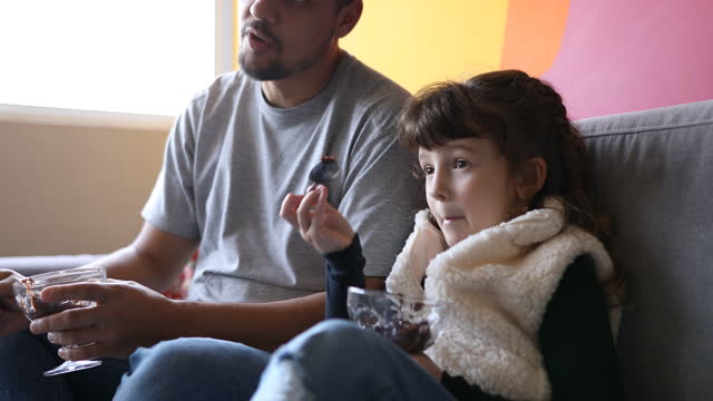 father and daughter eating sweets and watching tv - dia stock videos & royalty-free footage
