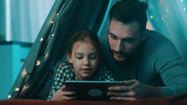 father and daughter enjoying at home temt - digital tablet stock videos & royalty-free footage