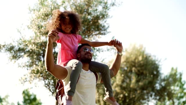 vídeos de stock e filmes b-roll de father and daughter enjoying summer day in the park - carregar uma pessoa nos ombros