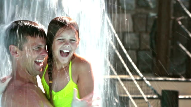 Father and daughter, fun under waterfall at water park