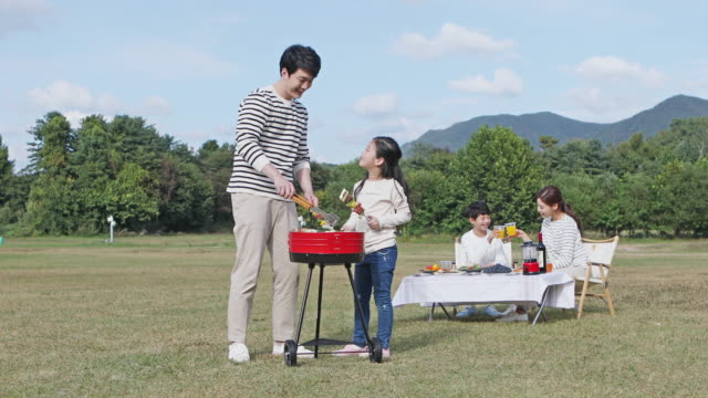 vídeos y material grabado en eventos de stock de father and daughter grilling meat for a family on the camping grounds - coreano oriental