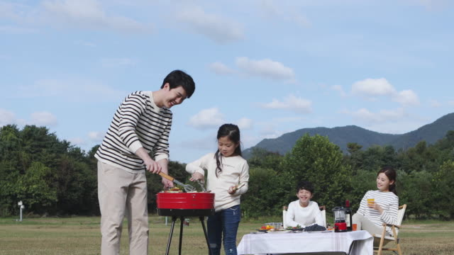 father and daughter grilling meat for a family on the camping grounds - koreanischer abstammung stock-videos und b-roll-filmmaterial