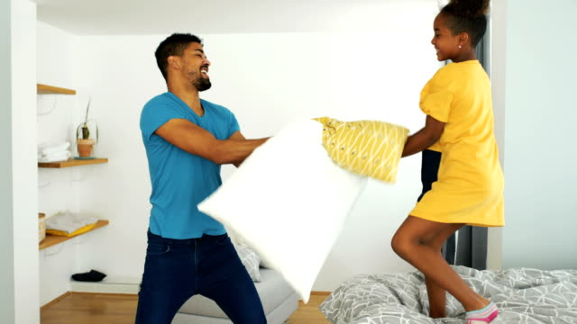 father and daughter having a pillow fight during coronavirus quarantine. - bedclothes stock videos & royalty-free footage