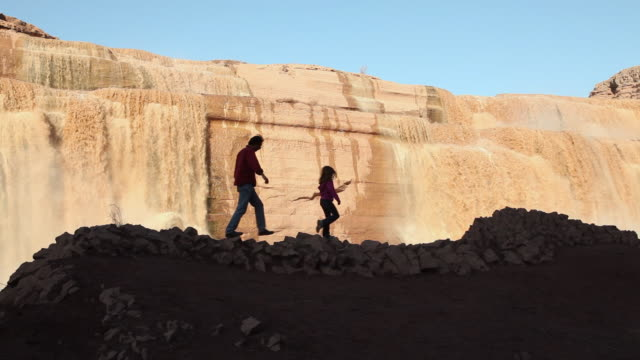 WS Father and Daughter (6-7) hiking along ledge against Grand Falls waterfall / Grand Falls, Arizona, USA