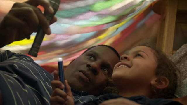 father and daughter in a blanket fort playing with flashlights. - bed sheets stock videos & royalty-free footage
