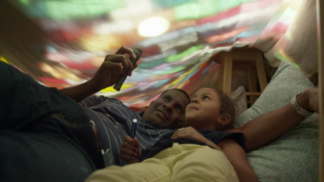 vidéos et rushes de father and daughter in a blanket fort playing with some flashlights. - oreiller