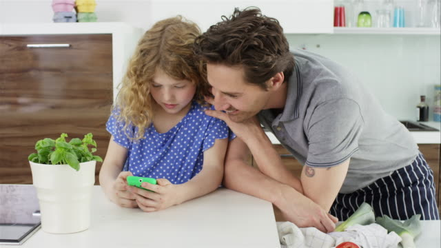 father and daughter in kitchen with smart-phone - kochrezept stock-videos und b-roll-filmmaterial