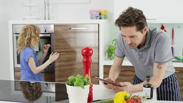 father and daughter in kitchen with tablet-computer - recipe stock videos & royalty-free footage