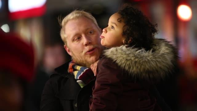 vídeos de stock, filmes e b-roll de pai e filha a olhar para as luzes de natal - safety
