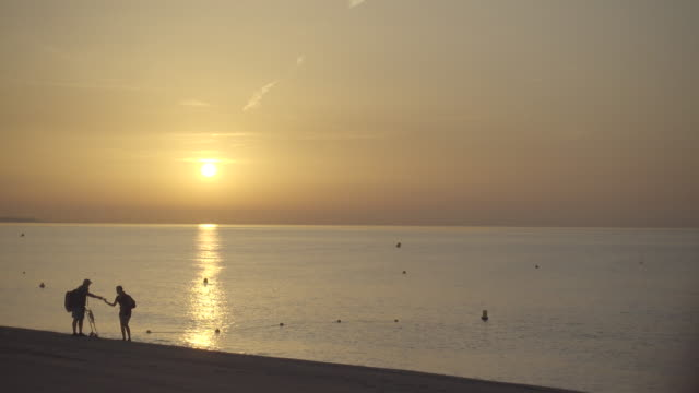 4k | father and daughter looking for treasure with a metal detector at an empty beach at the end of the summer. daybreak at mediterranean sea, spain catalan coast. we see their silhouette against the sun and sea backlight - 宝探し点の映像素材/bロール