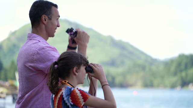 father and daughter looking through binoculars at view of lake connaught, washington, usa. - binoculars stock videos & royalty-free footage