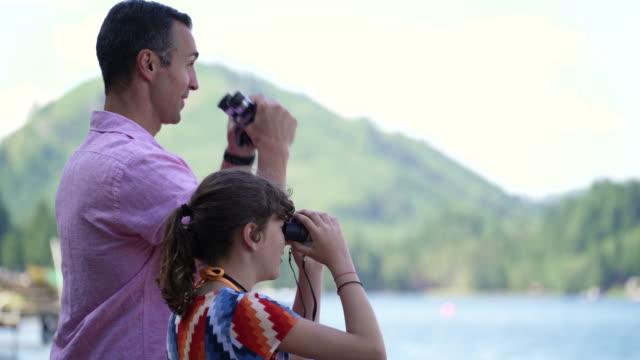 father and daughter looking through binoculars at view of lake connaught, washington, usa. - 双眼鏡点の映像素材/bロール