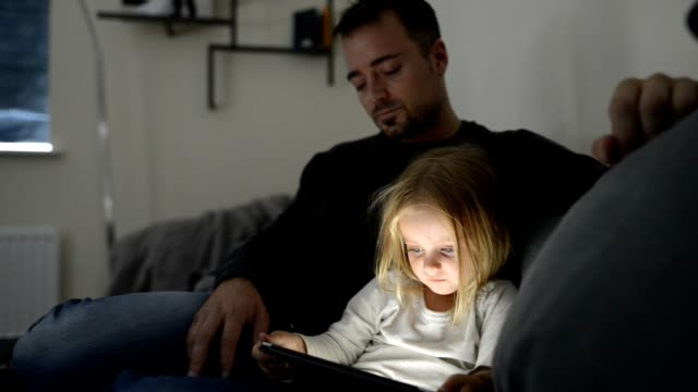 father and daughter looks on a digital tablet and sits on a couch - candid stock videos & royalty-free footage