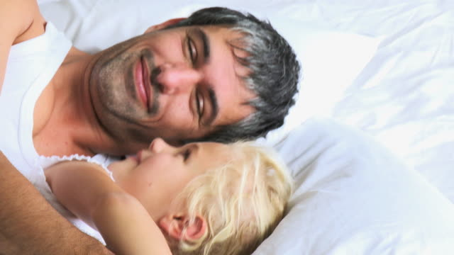 cu father and daughter (6-7) lying on bed / cape town, south africa - auf der seite liegen stock-videos und b-roll-filmmaterial