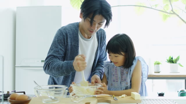 father and daughter making cake in sunlit japanese kitchen - making a cake stock videos and b-roll footage