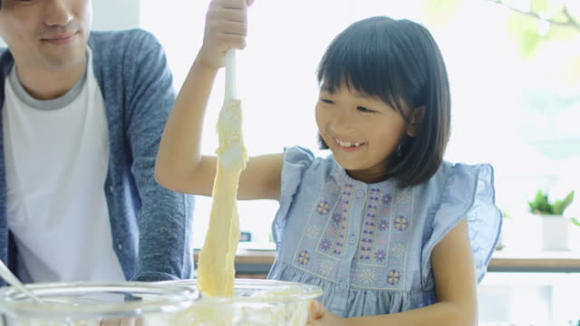 Father and Daughter Mixing Cake Together