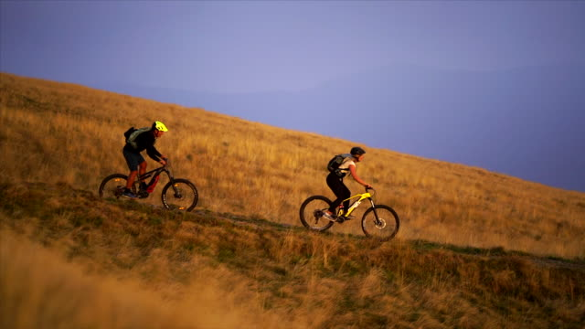 father and daughter mountain bikers ride trails at sunset - mountain bike video stock e b–roll