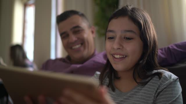vídeos de stock, filmes e b-roll de pai e filha em uma chamada de vídeo com um tablet digital em casa - 12 13 anos