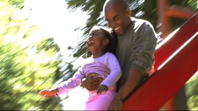 vidéos et rushes de father and daughter on slide - prendre sur les genoux
