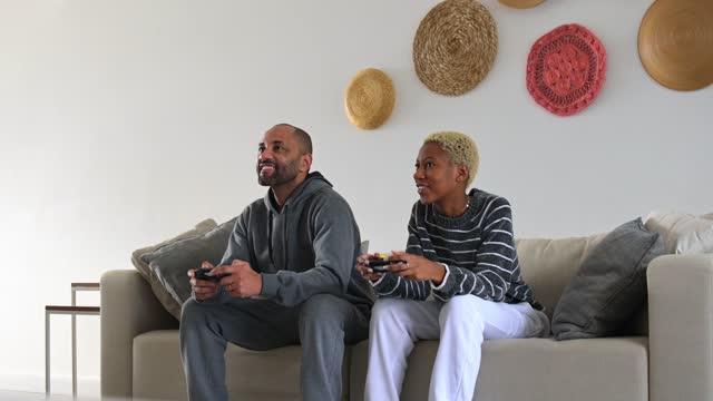 ビデオゲームをしているソファの上の父と娘 - dia点の映像素材/bロール