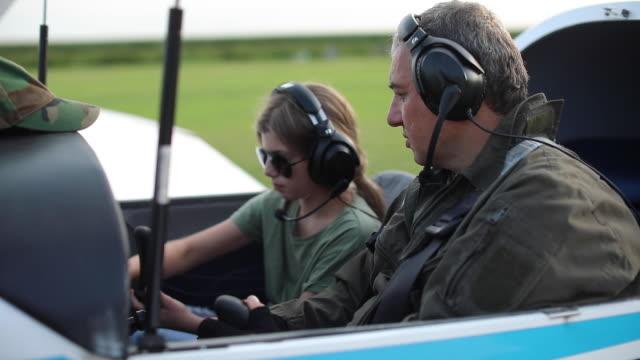 vidéos et rushes de pilotes de père et de descendant dans l'avion - transport aérien