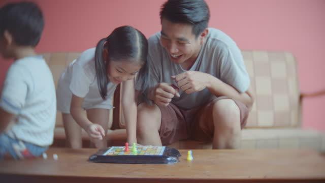 stockvideo's en b-roll-footage met vader en dochter spelen bordspel thuis, handheld schot - spelletjesavond