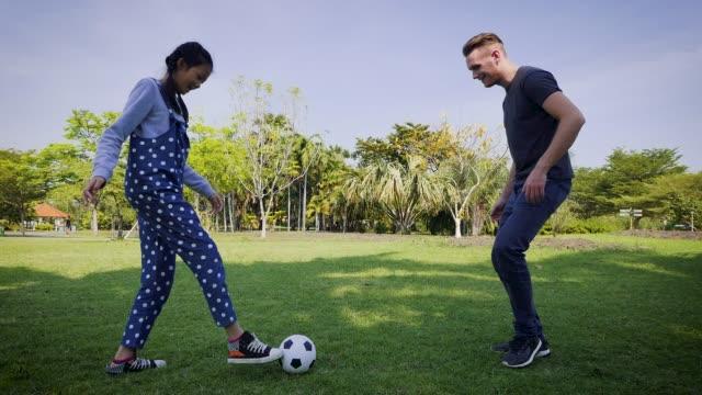 vidéos et rushes de père et fille jouant au football dans le parc à l'extérieur ensemble, saine de la vie sportive et le concept de famille - trentenaire