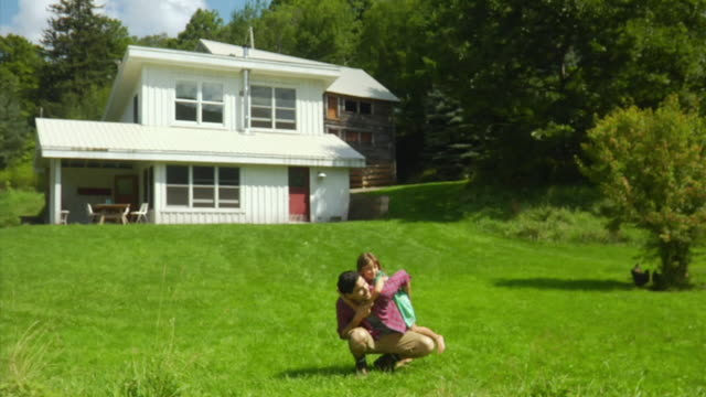 ws father and daughter (4-5) playing in front of house, bovina center, new york, usa - in front of stock videos & royalty-free footage