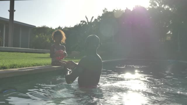 father and daughter playing in pool - freibad stock-videos und b-roll-filmmaterial