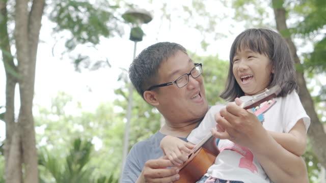 vídeos y material grabado en eventos de stock de padre e hija tocando el ukelele en el parque - father day