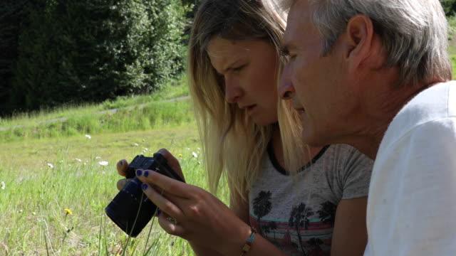 vídeos de stock, filmes e b-roll de o pai e a filha praticam usar a câmera no prado - cabelo grisalho