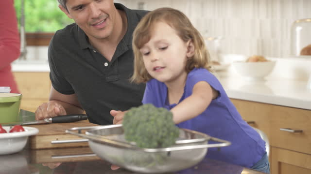 Father and daughter preparing broccoli for dinner