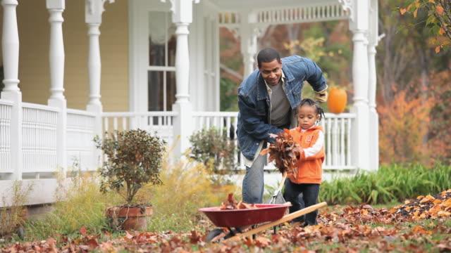vídeos de stock e filmes b-roll de ws pan td father and daughter (2-3) raking leaves in front yard of home / richmond, virginia, usa. - ancinho equipamento de jardinagem