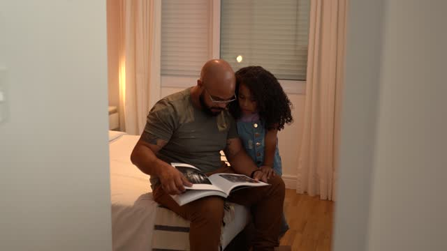 father and daughter reading a book at home - genderblend stock videos & royalty-free footage